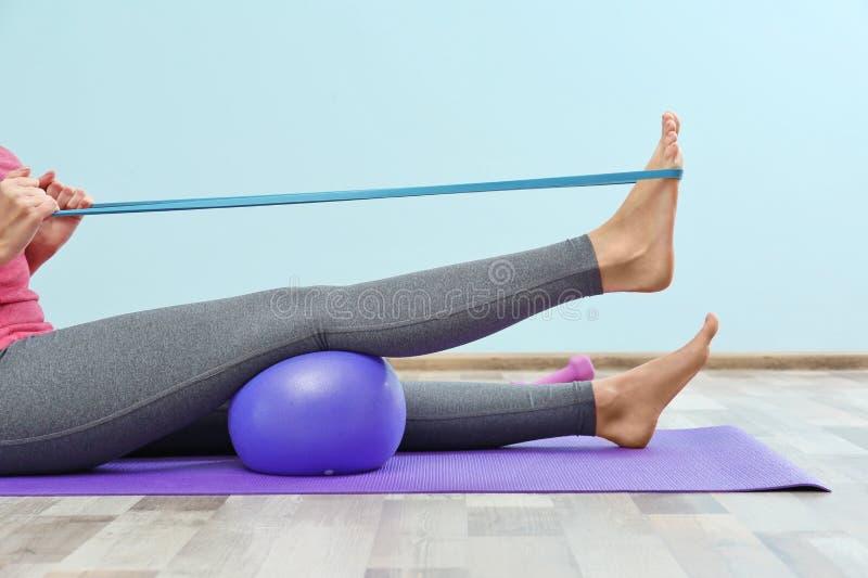 Тренировка женщины с эластичной резиновой лентой стоковое фото