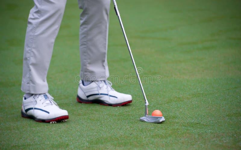 Тренировка и подогрев человека перед гольфом игры стоковая фотография