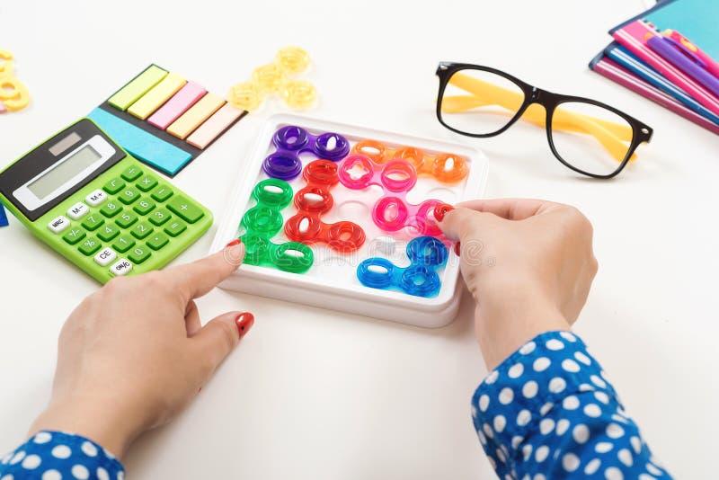 Тренировка логического мышления Женщина играет игру логики на ее рабочем месте Рука устанавливает последний элемент головоломки С стоковые изображения