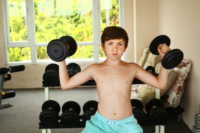 тренировка мальчика с гантелями в спортзале стоковое изображение