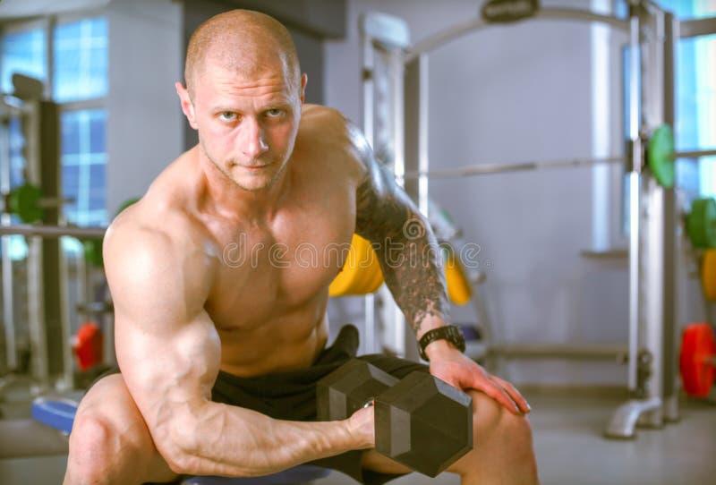 Тренировка молодого человека на спортзале с тренировками E стоковые фото