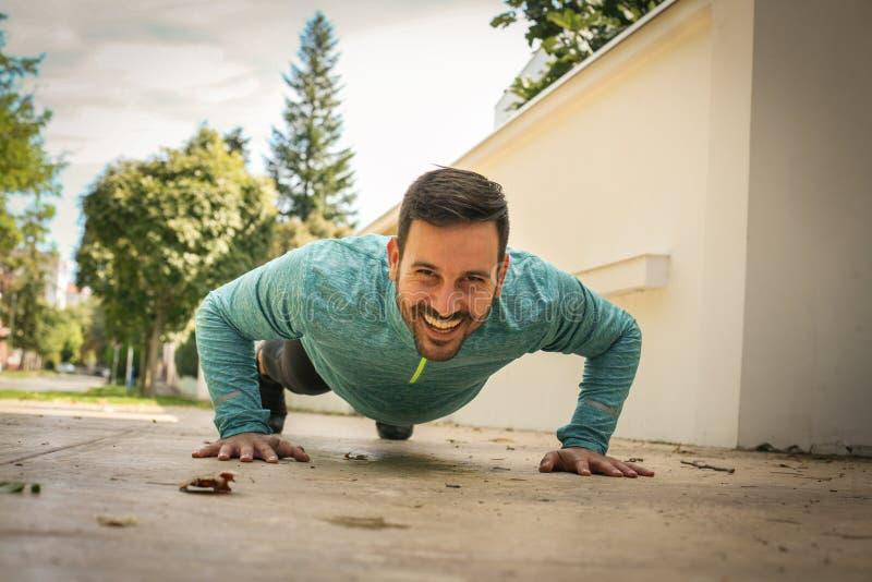 Тренировка молодого человека работая на тротуаре стоковые фото
