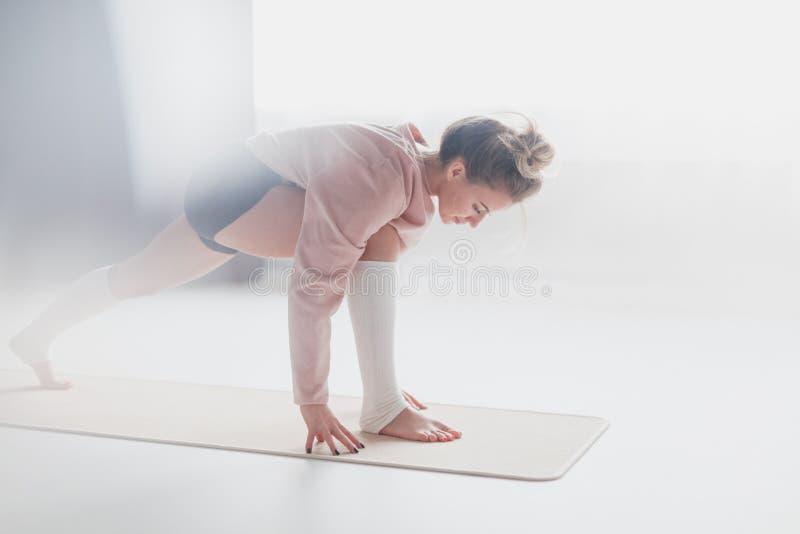 Тренировка молодой женщины на циновке йоги стоковые фото