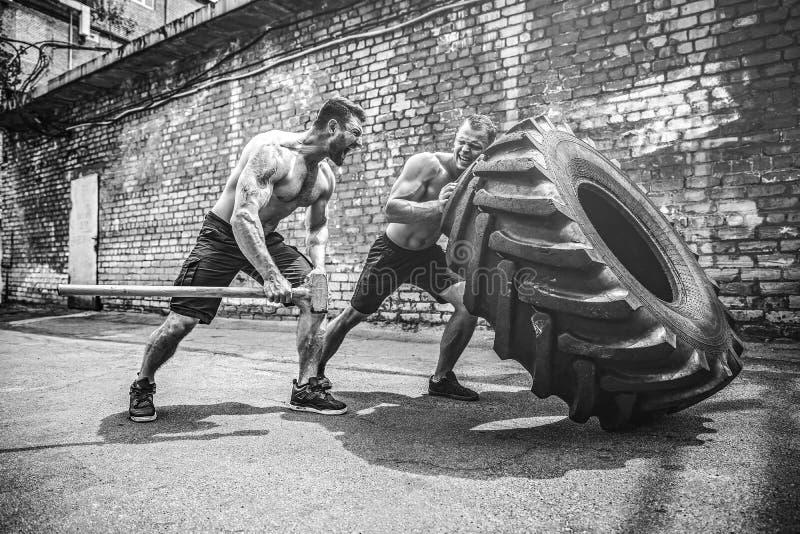 Тренировка 2 мышечная спортсменов Автошина мышечного человека фитнеса без рубашки moving большая стоковое фото