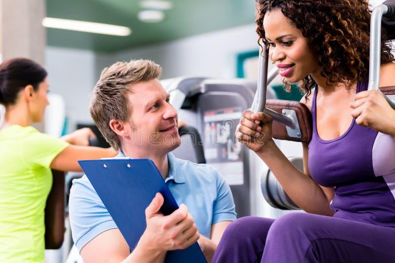 Тренировка фитнеса в спортзале - чернокожей женщине и личном тренере стоковая фотография rf