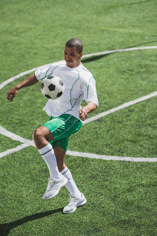Тренировка футболиста с шариком на тангаже футбола стоковое фото