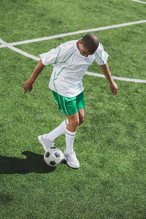 Тренировка футболиста с шариком на тангаже футбола стоковое фото rf