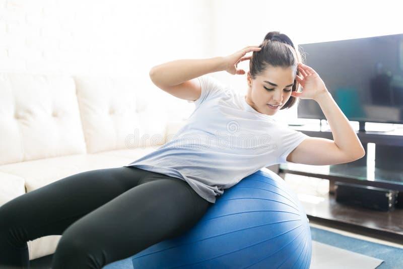 Тренировка шарика Pilates дома стоковые изображения rf