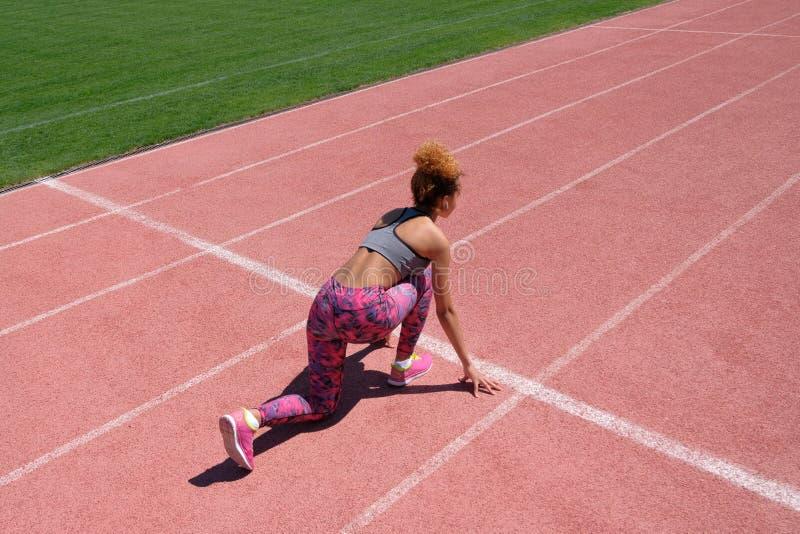 Тренировки спорт и протягивать или подготавливать бегуна начать на стадионе Молодая красивая темнокожая девушка в сером танке стоковые фотографии rf