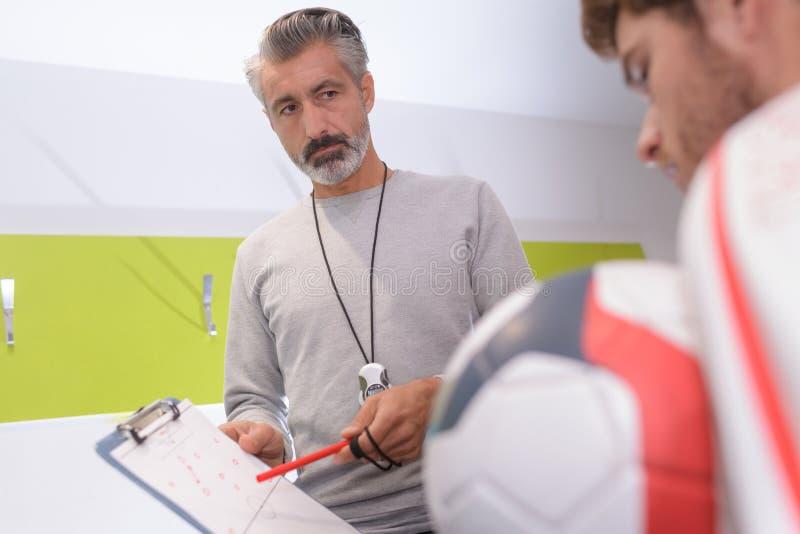 Тренируйте показывать диаграмму тактики футбола на бумаге над тангажом стоковые изображения rf