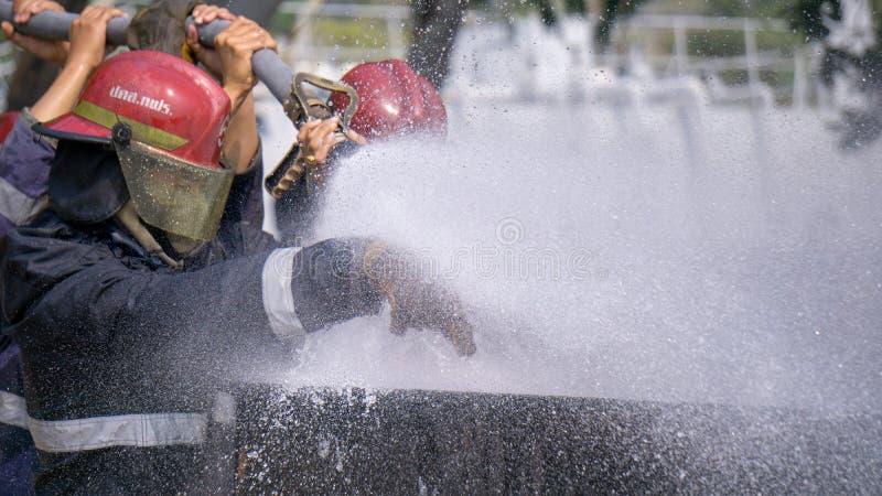 Тренирующие пожаротушения тушат огромный огонь с гидрантом воды стоковые изображения rf