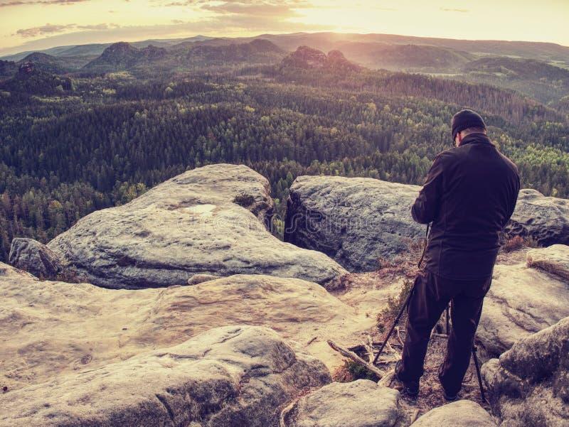 Тренога владением фотографа природы с камерой Человек на восходе солнца стоковое изображение rf