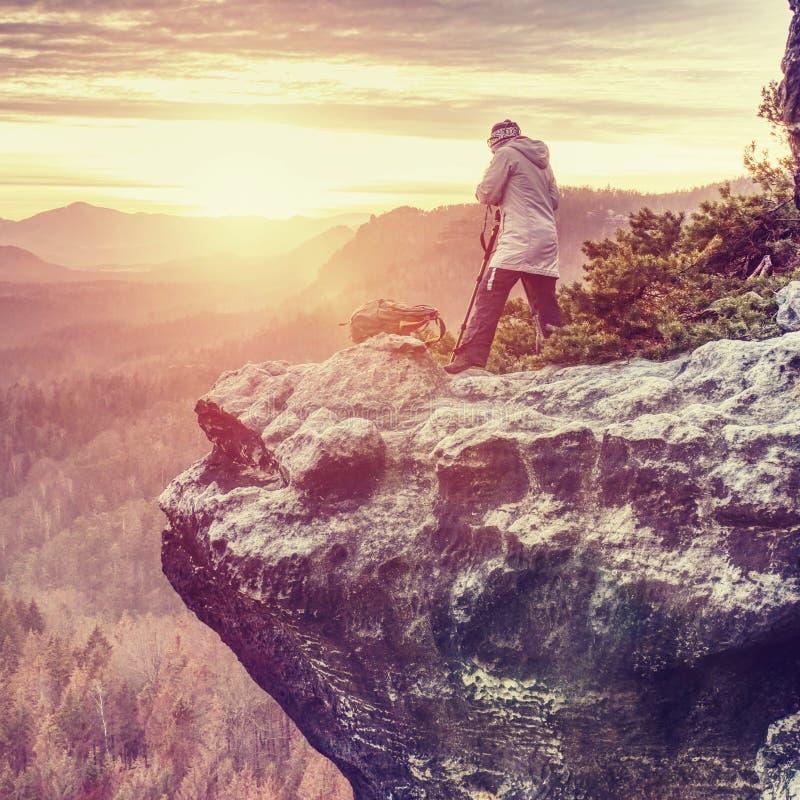 Тренога hiker женщины установленная с камерой на, который подвергли действию скалистом саммите стоковые изображения