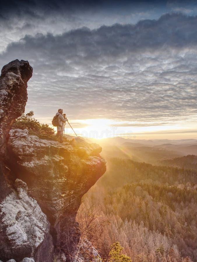Тренога hiker женщины установленная с камерой на, который подвергли действию скалистом саммите стоковая фотография rf