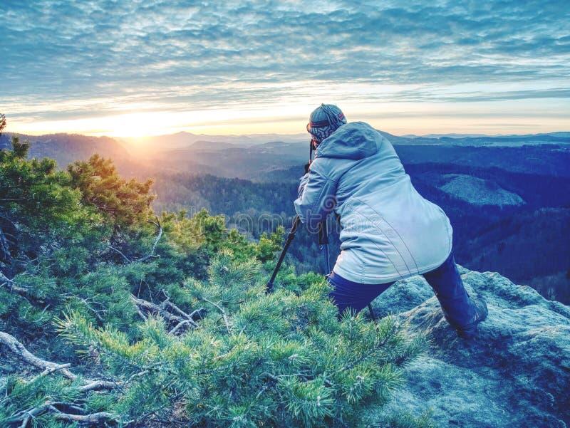 Тренога hiker женщины установленная с камерой на, который подвергли действию скалистом саммите стоковое фото