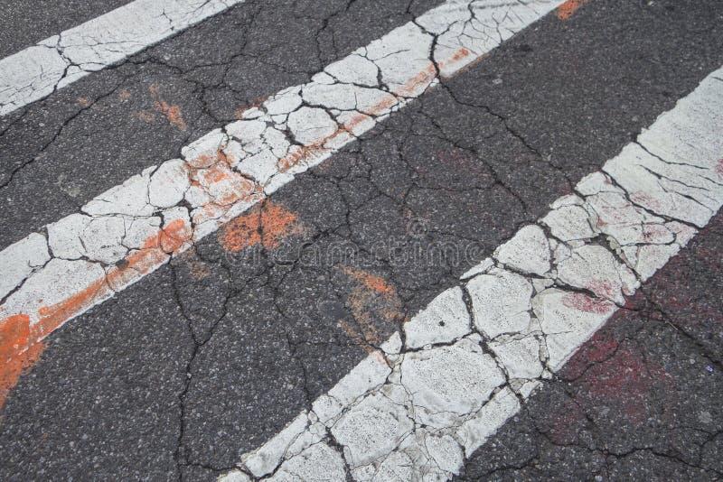Треская crosswalk blacktop гудронированного шоссе с белой линией оранжевыми маркировками краски города стоковое изображение