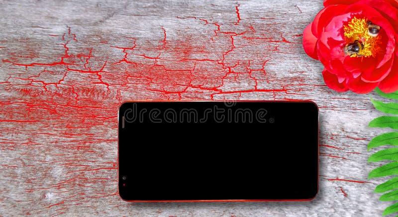 Треснутая деревянная текстура стола заполненная в светлом красном цвете с пустым темным экраном мобильного телефона, красного пио стоковое фото