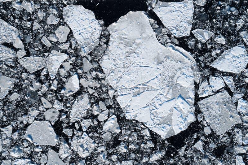 Треснутый лед плавая в темную воду стоковые изображения
