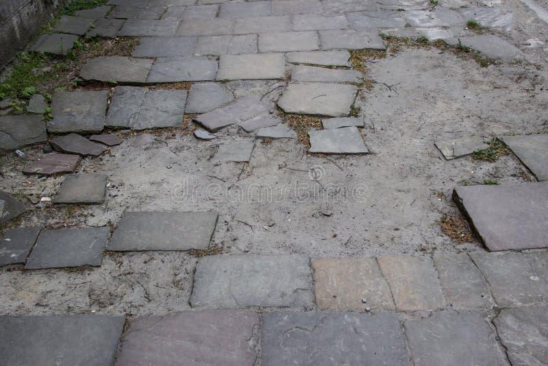 Треснутый тротуар, старая сломанная дорога мостоваой стоковая фотография rf