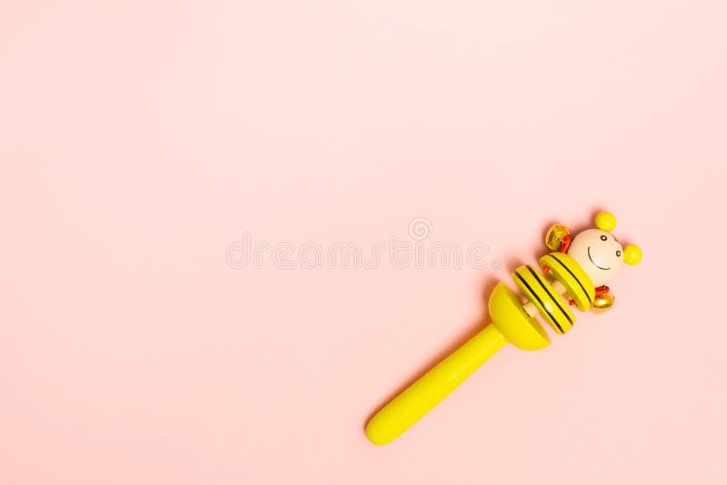 Трещотка младенца деревянная с колоколами металла для небольшого ребенка Желтая игрушка на розовой предпосылке с космосом экземпл стоковые изображения rf