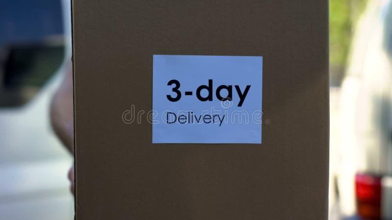 Тридневный курьер поставки в равномерной держа картонной коробке, качественном сервисе стоковое изображение