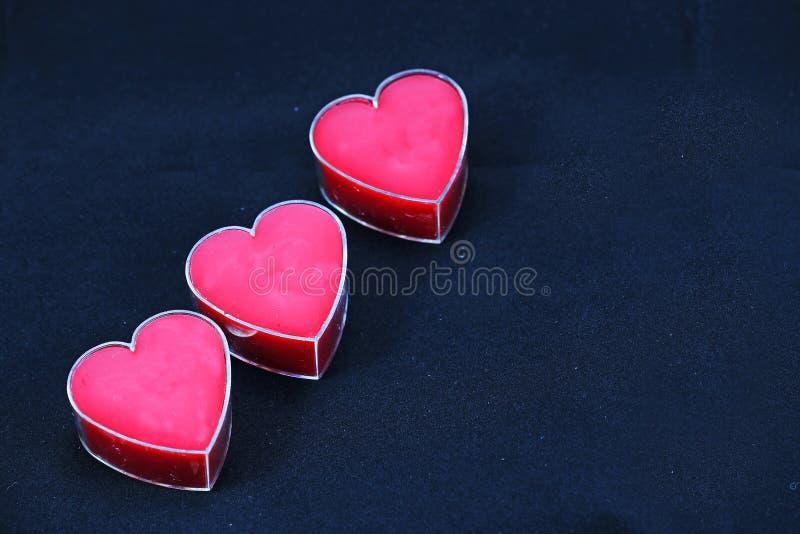 Трио розовых сердец на черной предпосылке стоковое изображение