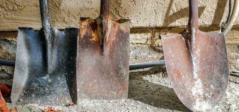 Трио старых, заржаветых лопаткоулавливателей которые все еще управляют получить работу сделанный стоковое изображение