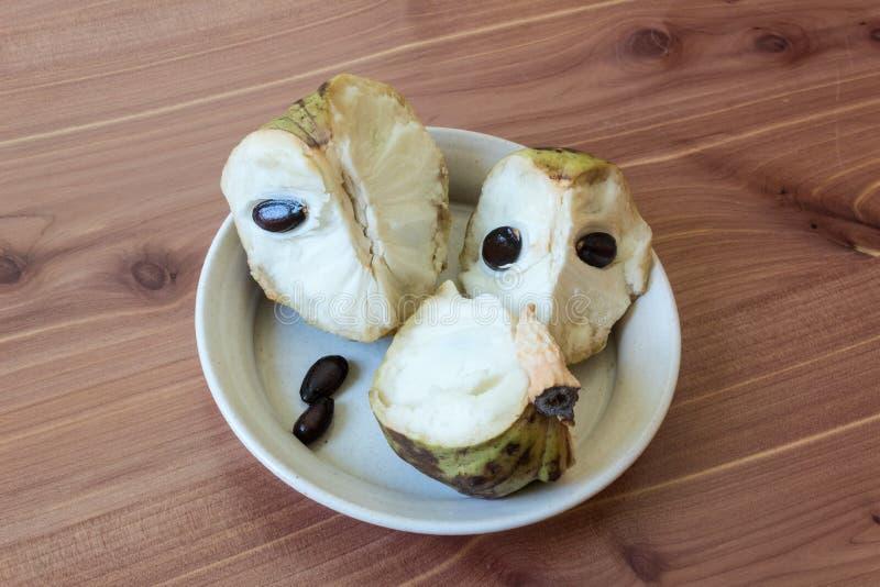 Трио частей зрелого плодоовощ annona cherimola cherimoya на центризованном отмелом блюде, подвергли действию семенах, который стоковое изображение rf