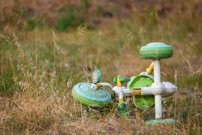 Трицикл ` s детей на лужайке Продемонстрируйте затерянность или выйдите стоковое изображение rf