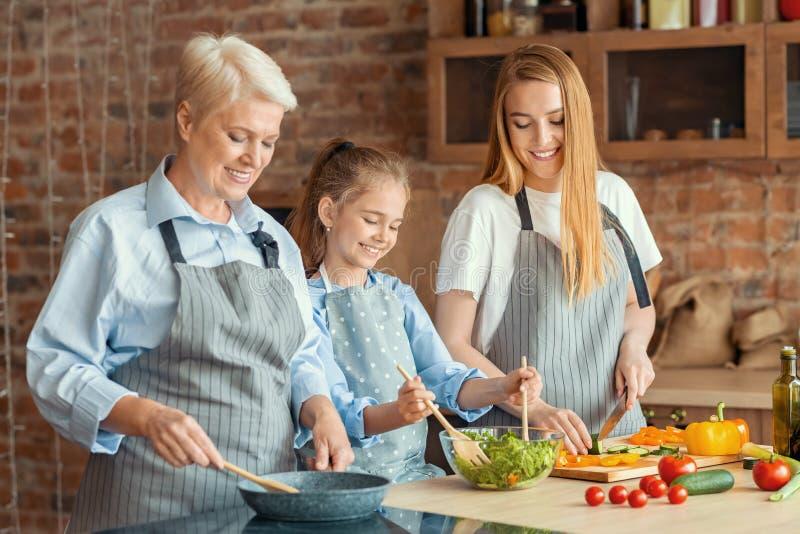 Три поколения женщин вместе готовят здоровый ужин стоковые фото
