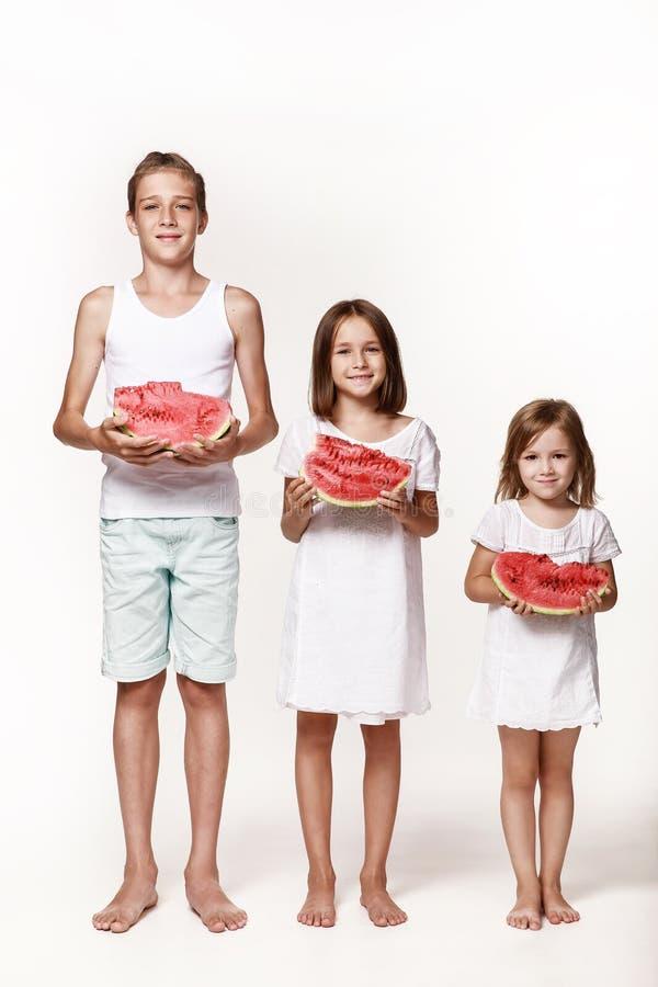 Три ребенка в студии стоят на белом фоне и держат кусочки арбуза стоковая фотография