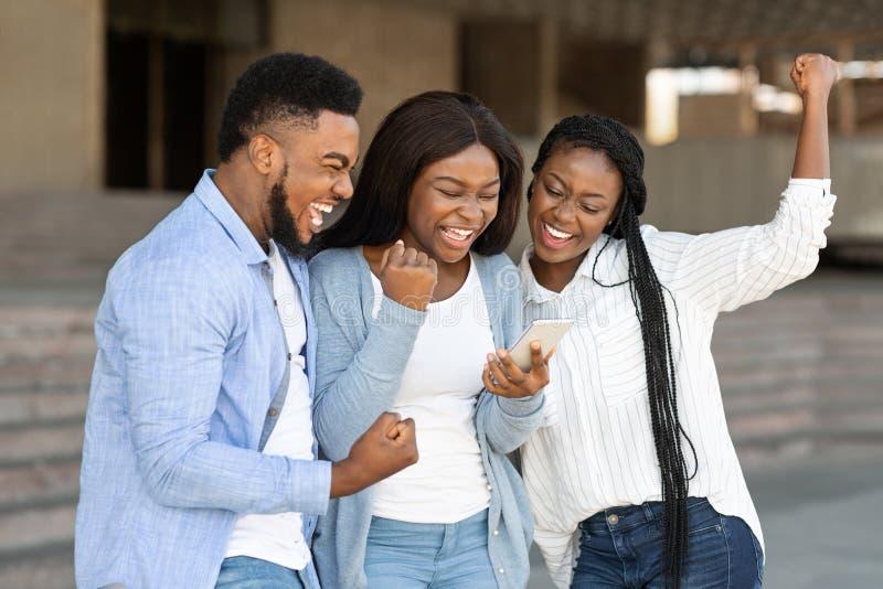 Три счастливых афро-американских друга празднуют успех на открытом воздухе благодаря смартфону стоковые изображения rf