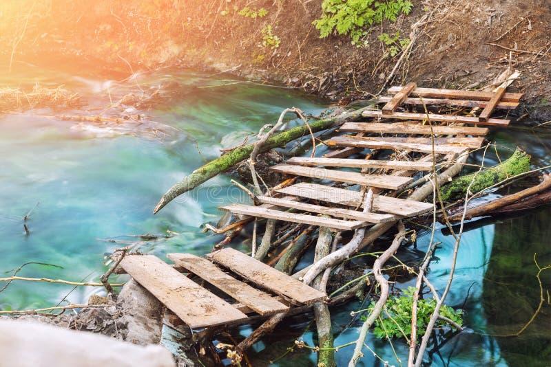 Тропа через сценарный красивый старый деревянный мост планки над чистым потоком горы с ясной водой бирюзы Спокойный стоковые фото