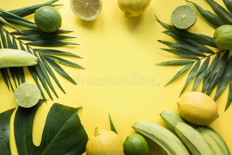 Тропическая граница плодов, банан, известка, выходит ладони на желтую предпосылку   Путешествие вытрезвителя стоковое фото