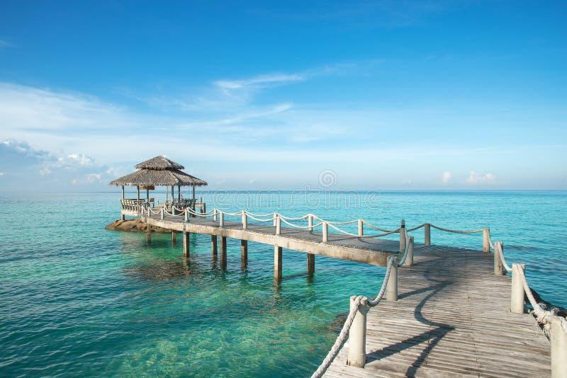 Тропическая хата и деревянный мост на курорте - vacati лета стоковые изображения