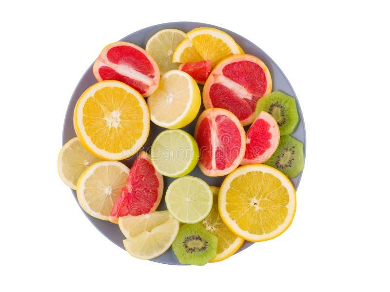 Тропические плодоовощи лежат в плите на предпосылке изолированной белизной над взглядом стоковая фотография rf