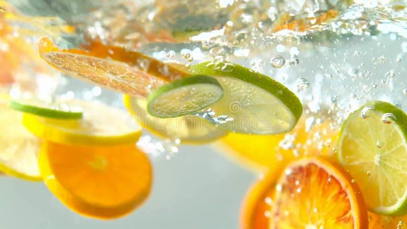 Тропические плоды citurs отрезают падать в воду стоковые фотографии rf