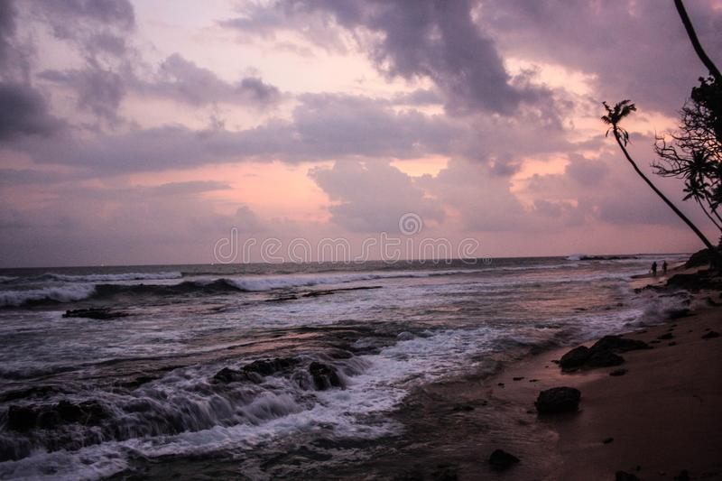 Тропический заход солнца с силуэтами пальмы и волнами Индийского океана Солнце, небо, море, волны и песок стоковая фотография