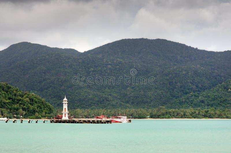 Тропический ландшафт с морем бирюзы тропическим, белым маяком, рыбацкой лодкой, пристанью Bao челки и островом Chang Koh на гориз стоковая фотография rf