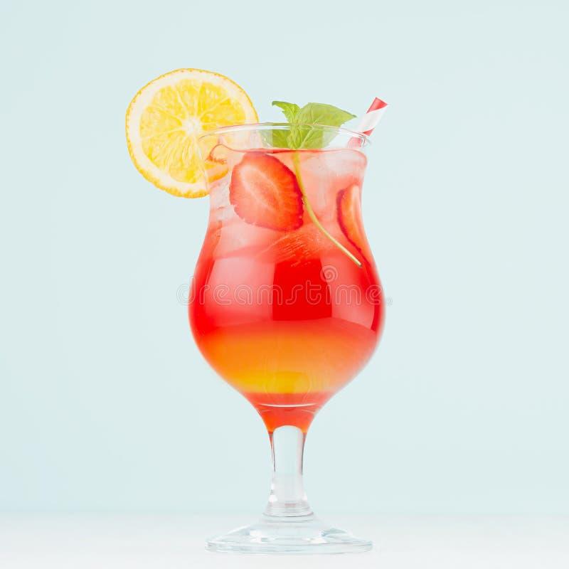 Тропический освежая striped восход солнца с апельсинами кусков, лед напитка плода, клубника, мята в рюмке на пастельном зеленом и стоковое фото