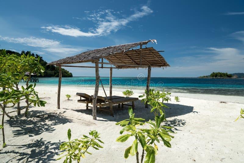 Тропический пляжный комплекс песка на удаленном острове Malenge, часть архипелага Togean с укрытием и deckchair стоковое изображение rf