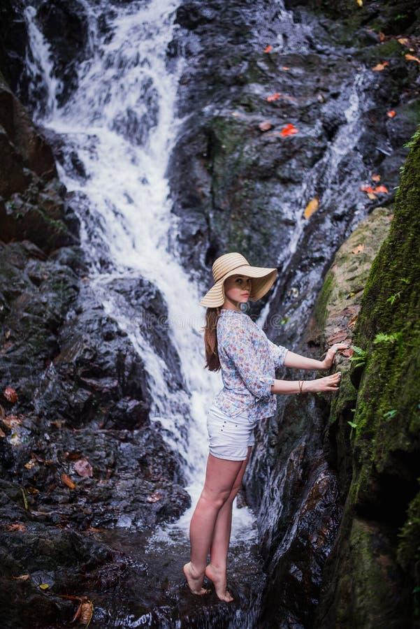 Тропический путешествовать Молодая женщина в шляпе наслаждаясь взглядом водопада стоковое фото