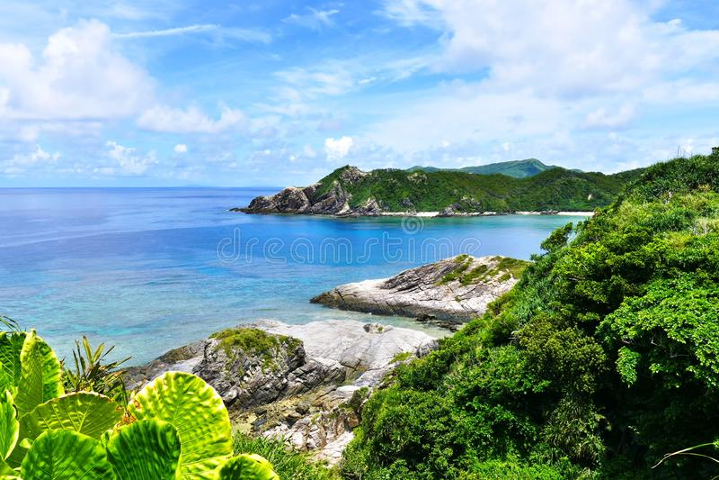 Тропический рай зеленых холмов, белого песка, моря бирюзы и темносинего солнечного неба на Zamami, Окинава, Японии стоковое изображение