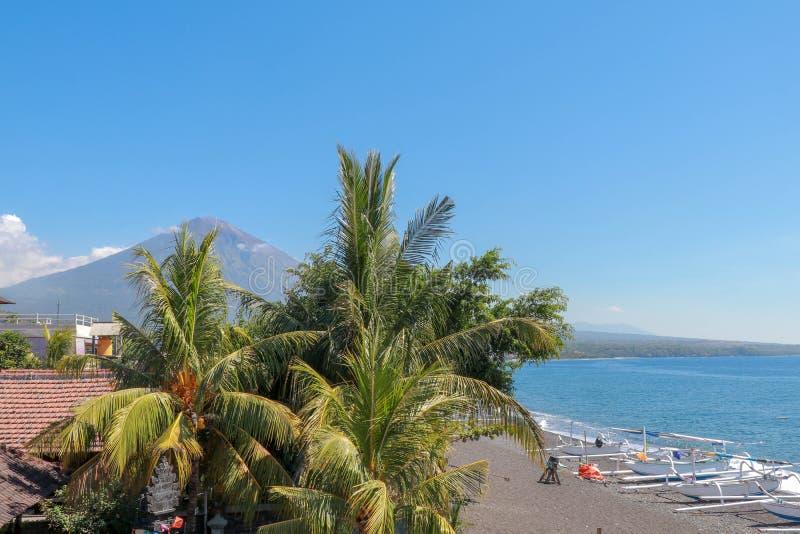 Тропический рай с пальмами и величественным вулканом на заднем плане Белые облака вокруг кратера вулкана стоковые изображения