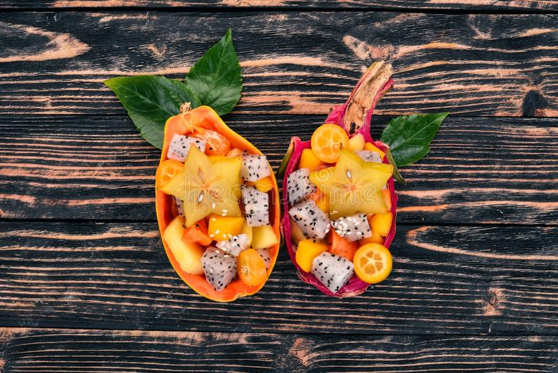 Тропический фруктовый салат служил в половине папапайи Плод дракона, рамбутан, тамаринд, плод кактуса, авокадо, манго стоковое изображение