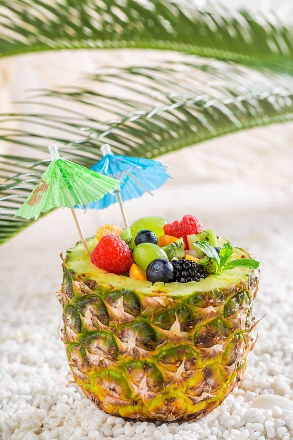 Тропический фруктовый салат в ананасе с зонтиками коктеиля стоковые изображения rf