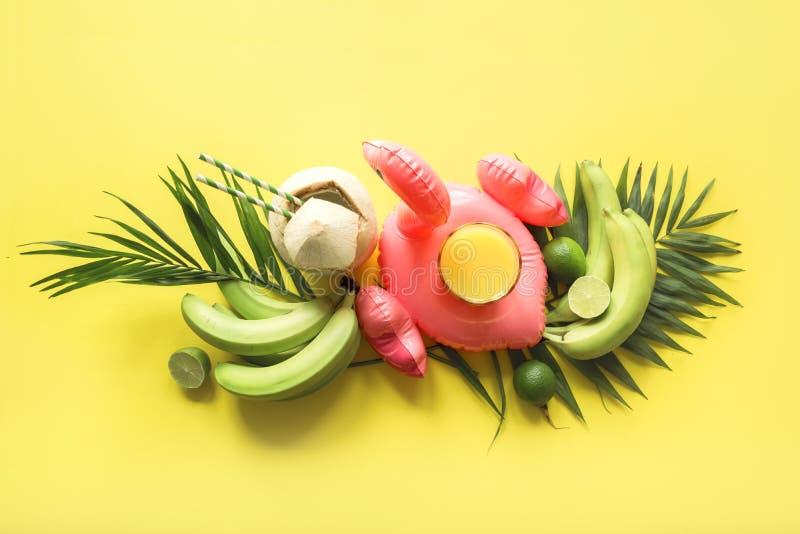 Тропическое знамя плодов, банан, известка, ладони листьев, апельсиновый сок в раздувном розовом фламинго, свежем кокосе на напори стоковое изображение rf
