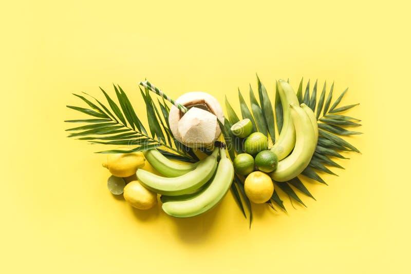 Тропическое знамя плодов, банан, известка, ладони листьев, свежий кокос на напористой желтой предпосылке   Путешествие вытрезвите стоковое изображение rf