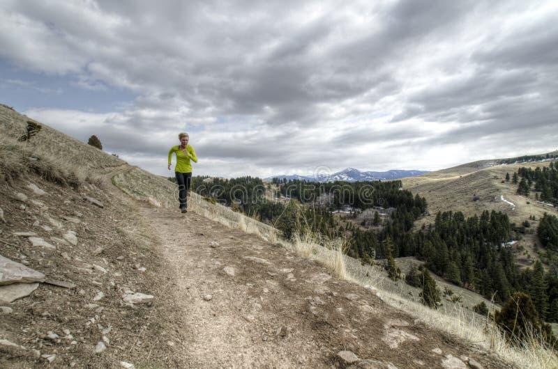 Тропка женщины бежать в горах стоковые изображения