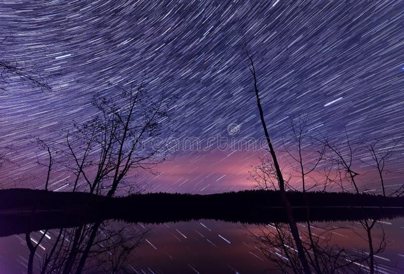 Тропки звезды вдоль озера с деревьями стоковая фотография